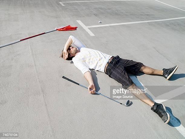 Golfer lying in car park