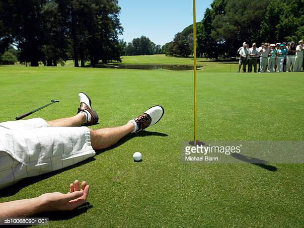 Golfer lying on course (low section), people in background