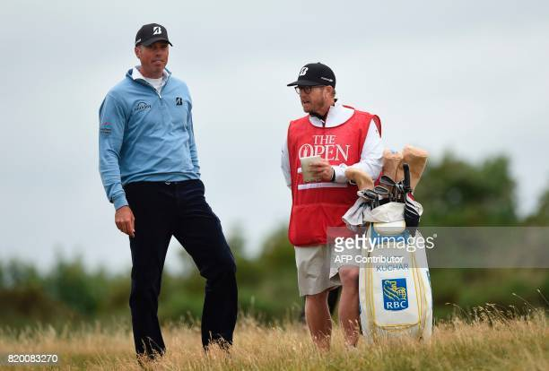 US golfer Matt Kuchar and his caddie John Wood talk in the rough on the 8th hole during his second round on day two of the Open Golf Championship at...