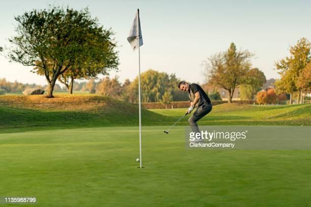 golfer verpasst seinen putt. - einlochen golf stock-fotos und bilder
