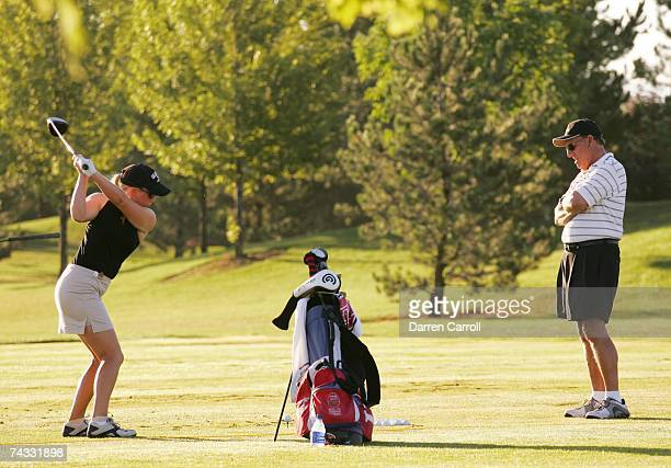 Golfer Morgan Pressel warms up on the driving range while her her grandfather Herb Krickstein watches before the quarterfinals of the US Girls'...