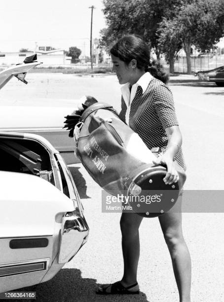 Golfer Nancy Lopez of the United States puts her golf bag in the trunk of her car on July 28, 1973 in Tucson, Roswell, New Mexico.