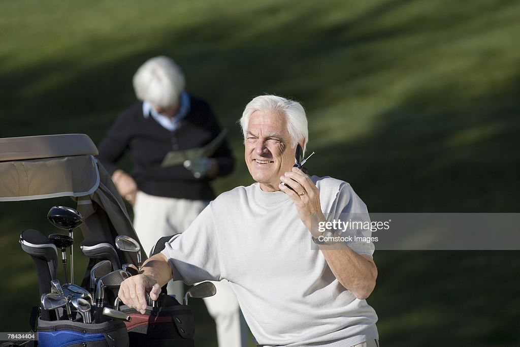 Golfer on cell phone : Stockfoto