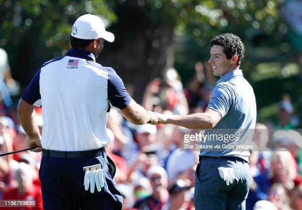 USA golfer Patrick Reed and European Rory McIlroy show respect to each other as they matched birdies during the Sunday morning match play ] JERRY...