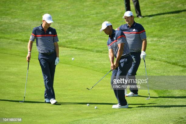 US golfer Patrick Reed and US golfer Justin Thomas look on as US golfer Tiger Woods plays a chip shot uring a practice session ahead of the 42nd...