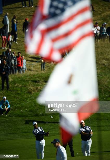 US golfer Patrick Reed and US golfer Tiger Woods plays shots during a practice session ahead of the 42nd Ryder Cup at Le Golf National Course at...