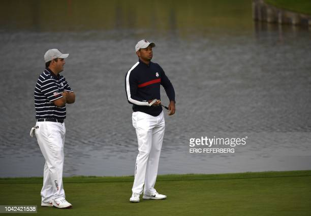 US golfer Patrick Reed and US golfer Tiger Woods speak during their fourball match on the first day of the 42nd Ryder Cup at Le Golf National Course...