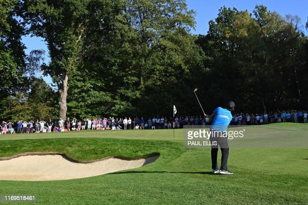 US golfer Patrick Reed chips onto the 15th green on day one of the golf PGA Championship at Wentworth Golf Club in Surrey south west of London on...