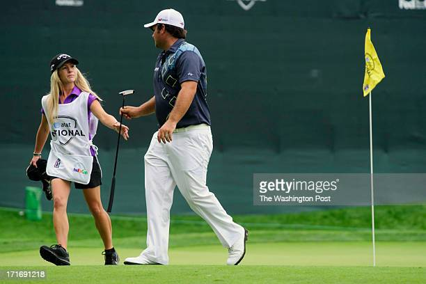 Golfer Patrick Reed hands his golf club to his wife, Justine Karain, who serves as his caddy at the tenth hole of the Congressional Country Club golf...