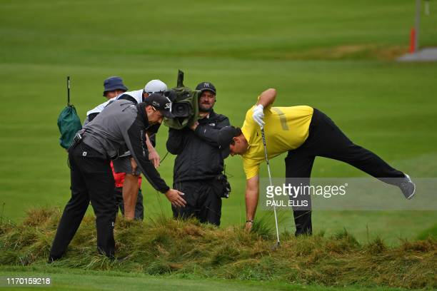 US golfer Patrick Reed looks for his ball in the rough on the 4th hole on Day 4 of the golf PGA Championship at Wentworth Golf Club in Surrey south...
