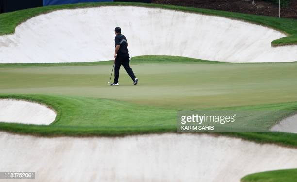 US golfer Patrick Reed moves to play a shot between bunkers during the DP World Tour Championship at Jumeirah Golf Estates in Dubai on November 21...