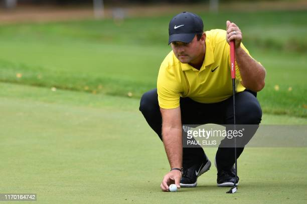 US golfer Patrick Reed places his ball on the 4th green on Day 4 of the golf PGA Championship at Wentworth Golf Club in Surrey south west of London...