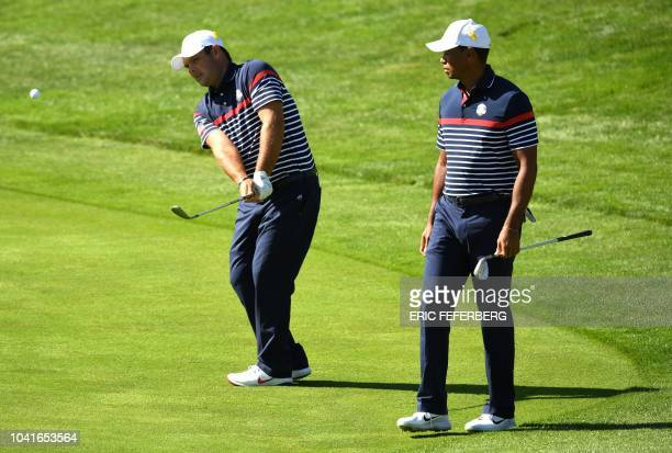 US golfer Patrick Reed plays a chip shot as US golfer Tiger Woods looks on uring a practice session ahead of the 42nd Ryder Cup at Le Golf National...