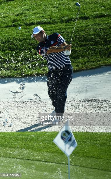 US golfer Patrick Reed plays a shot out of a bunker during a practice session ahead of the 42nd Ryder Cup at Le Golf National Course at...
