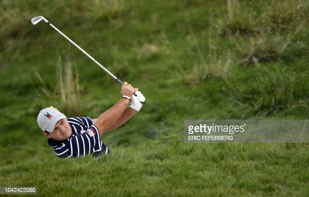 US golfer Patrick Reed plays a shot out of a bunker during his fourball match on the first day of the 42nd Ryder Cup at Le Golf National Course at...
