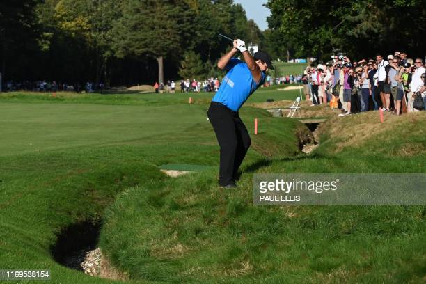 US golfer Patrick Reed plays from the rough on the 15th hole on day one of the golf PGA Championship at Wentworth Golf Club in Surrey south west of...