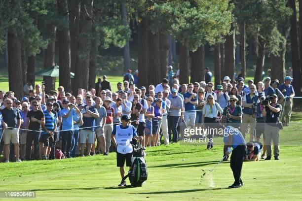 US golfer Patrick Reed plays his approach shot from the 13th fairway on day one of the golf PGA Championship at Wentworth Golf Club in Surrey south...