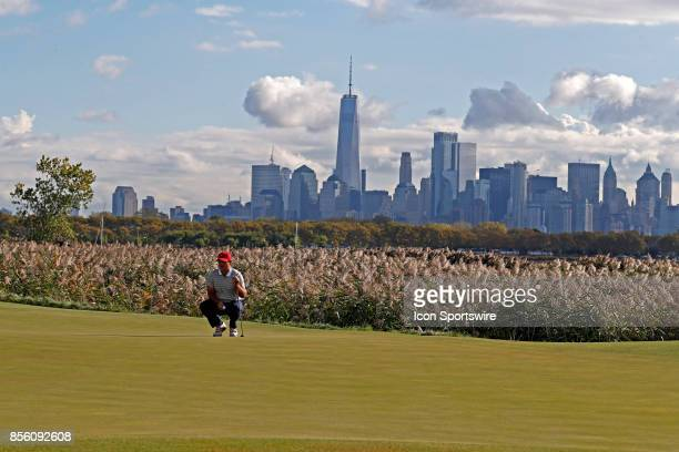 USA golfer Patrick Reed putts on the 10th hole with the New York city skyline in the background during the third round of the Presidents Cup at...