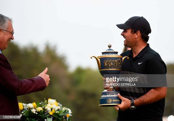 US golfer Patrick Reed smiles after receiving the trophy from Mexican businessman Ricardo Salinas Pliego after winning the World Golf Championship at...