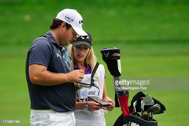 Golfer Patrick Reed talks with his wife Justine Karain who serves as his caddy at the 11th hole of the Congressional Country Club golf course during...
