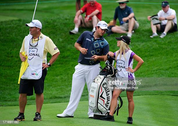 Golfer Patrick Reed talks with his wife, Justine Karain, who serves as his caddy at the 11th hole of the Congressional Country Club golf course...