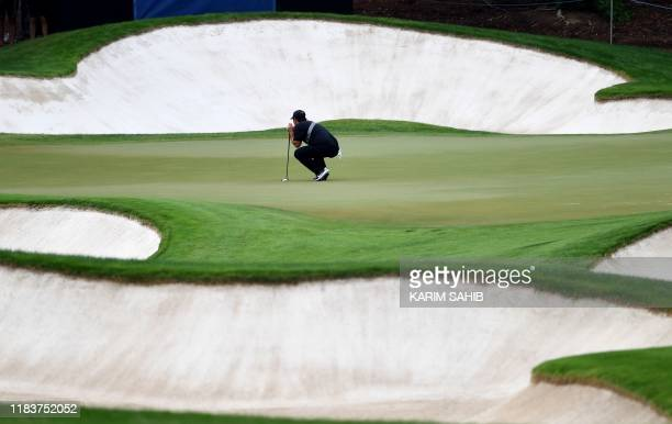 US golfer Patrick Reed visualizes a shot between bunkers during the DP World Tour Championship at Jumeirah Golf Estates in Dubai on November 21 2019