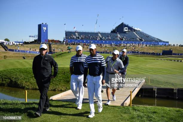 Golfer Patrick Reed walks with US golfer Tiger Woods during a practice session ahead of the 42nd Ryder Cup at Le Golf National Course at...