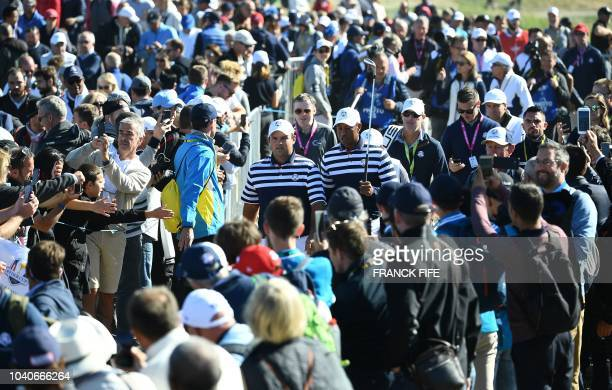 US golfer Patrick Reed walks with US golfer Tiger Woods during a practice session ahead of the 42nd Ryder Cup at Le Golf National Course at...