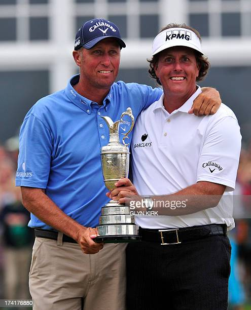 US golfer Phil Mickelson holds the Claret Jug as he poses with his caddie Jim Mackay after winning the 2013 British Open Golf Championship at...
