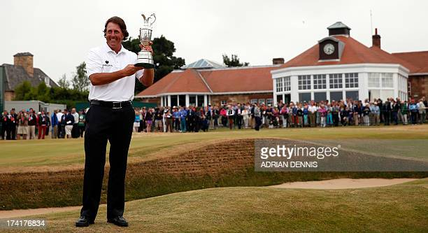 US golfer Phil Mickelson holds the Claret Jug in front of the club house after winning the 2013 British Open Golf Championship at Muirfield golf...
