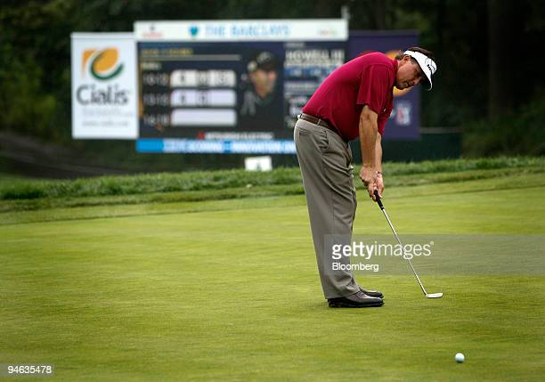 Golfer Phil Mickelson makes a putt in front of an LED scoreboard displaying statistics supplied by SHOTLink during the Barclays Classic golf...