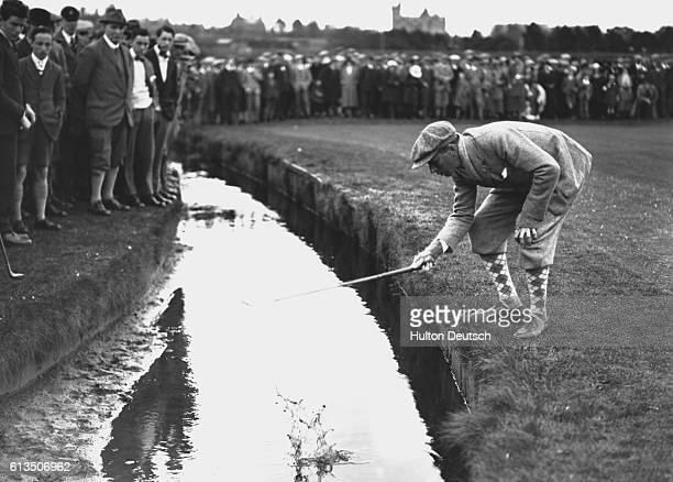 Golfer Picking His Ball Out of Water Hazard