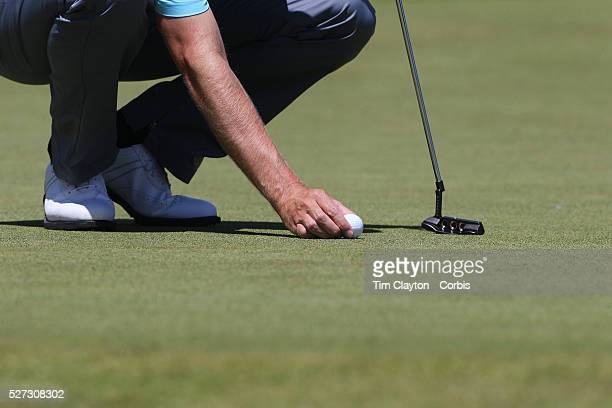 A golfer places his ball before putting Photo Tim Clayton