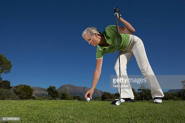 golfer placing ball on tee - older woman bending over stock pictures, royalty-free photos & images