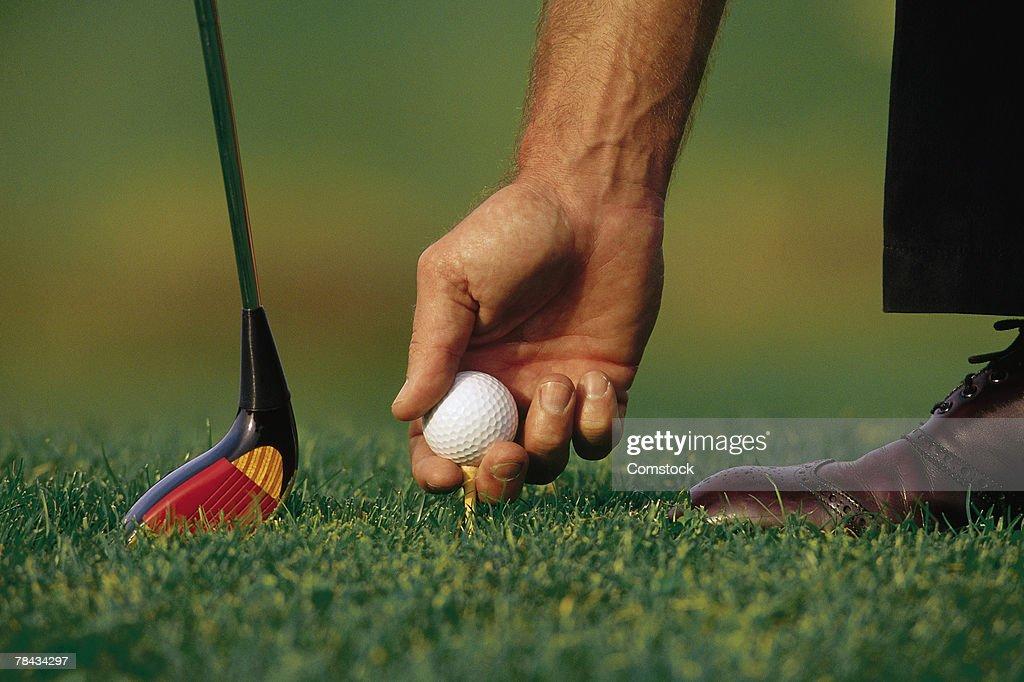 Golfer placing ball on tee : Stockfoto