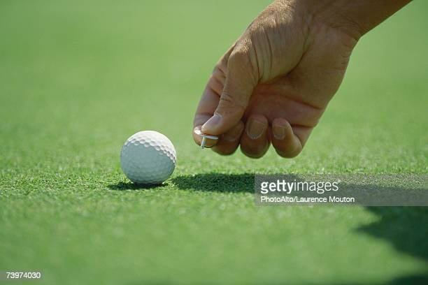 Golfer placing golf ball marker on turf, close-up of hand