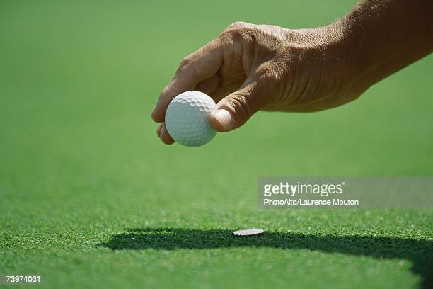 Golfer placing golf ball on turf, close-up of hand