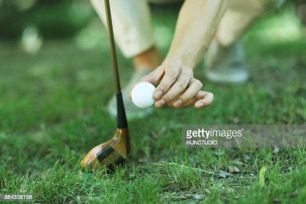 Golfer placing golf ball
