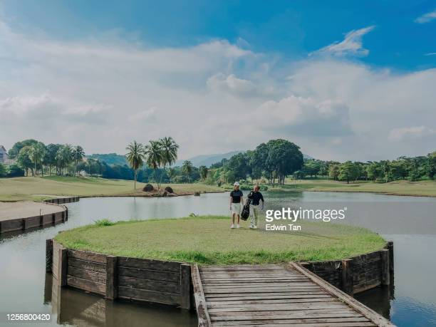 golfer playing golf in golf course in melaka, malaysia walking toward carrying golf set - golf stock pictures, royalty-free photos & images