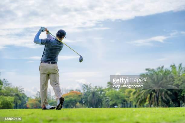 golfer playing golf on a golf course - ゴルフのスウィング ストックフォトと画像