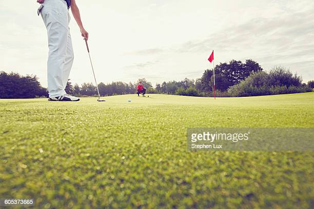 Golfer playing near hole, Korschenbroich, Dusseldorf, Germany