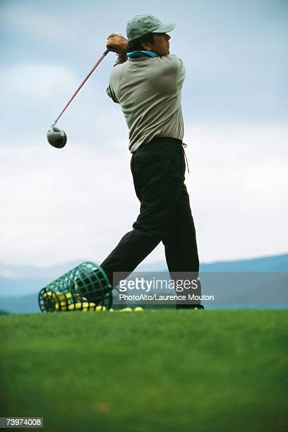 Golfer practicing on driving range, low angle view