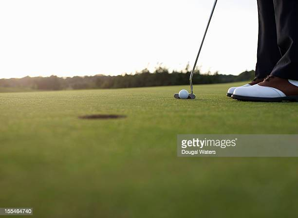 golfer preparing to putt ball towards hole. - putting stock pictures, royalty-free photos & images