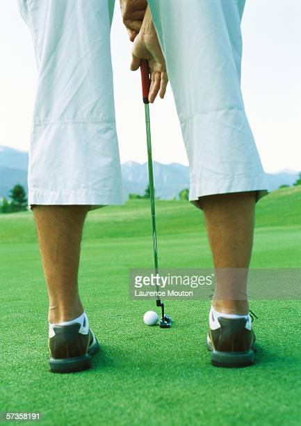 Golfer preparing to swing, low section, rear view