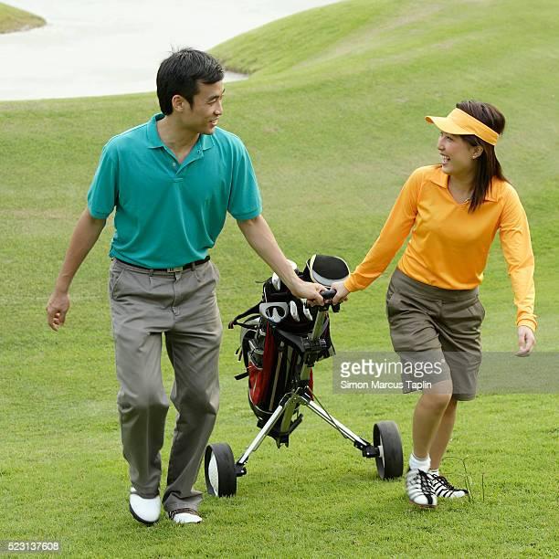 Golfer Pulling Bag Together