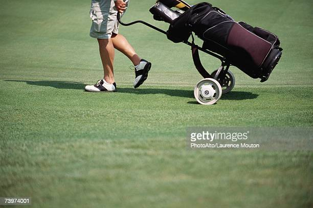 Golfer pulling caddy