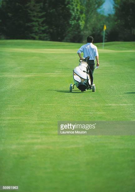 Golfer pulling golf bag on green