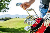 Golfer Pulling Out a Golf Club From Red Golf Bag