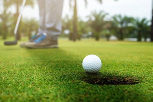 golfeur mettant la balle de golf à l'approche du trou de golf sur le golf vert.  - photos et images libres de droits de Golf Action
