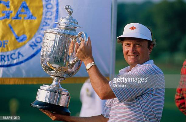 Golfer Ray Floyd smiles as he holds the PGA Championship Trophy